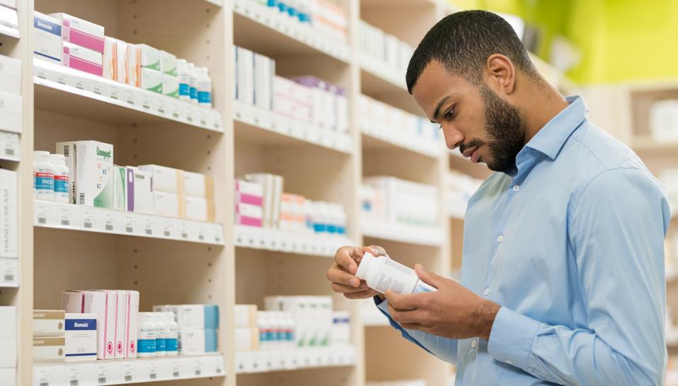 Beard Man Choosing Supplement In Drugstore