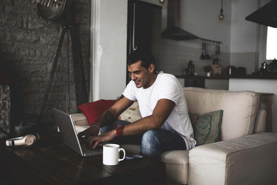 Smiling young man sitting on sofa at home using laptop