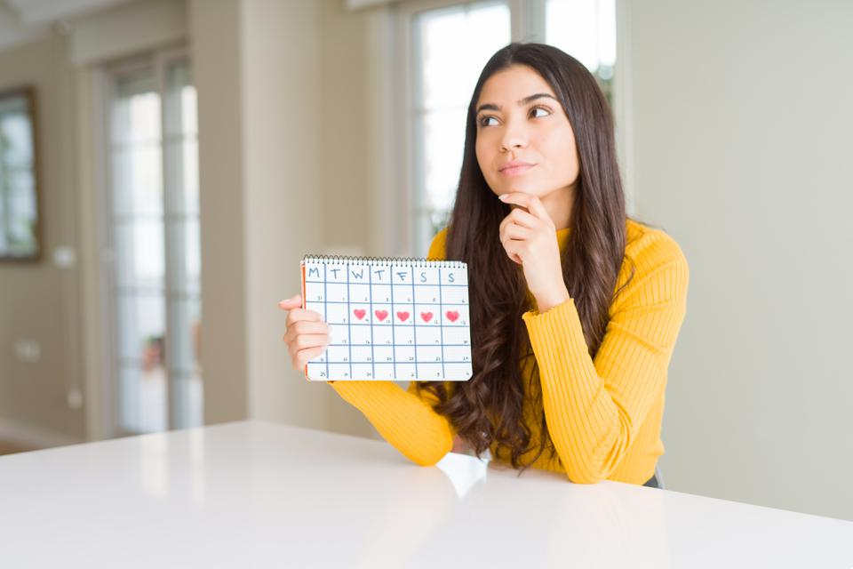 Young woman holding menstruation calendar