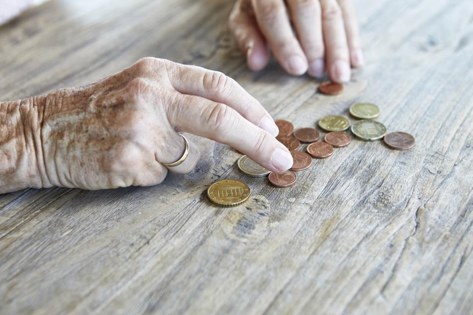 Hand of senior woman counting coins, close-up