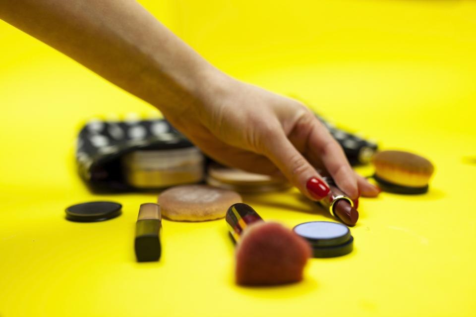Hand Reaching For Lipstick From a Make Up Bag On Yellow Background.