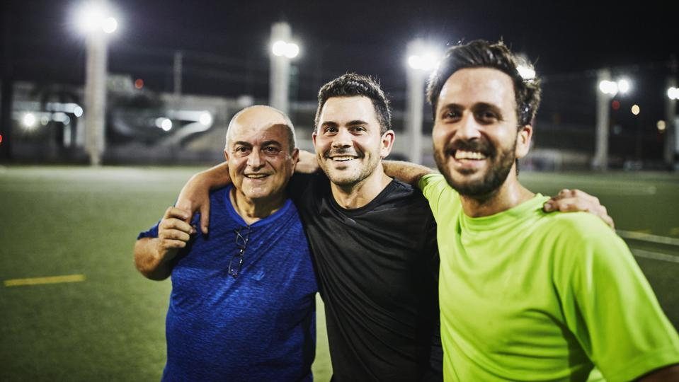 Smiling mature man embracing adult sons after evening soccer match