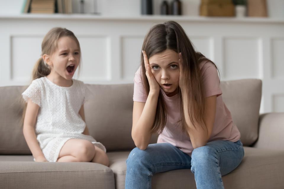 Stressed mother feeling desperate about screaming stubborn kid daughter tantrum