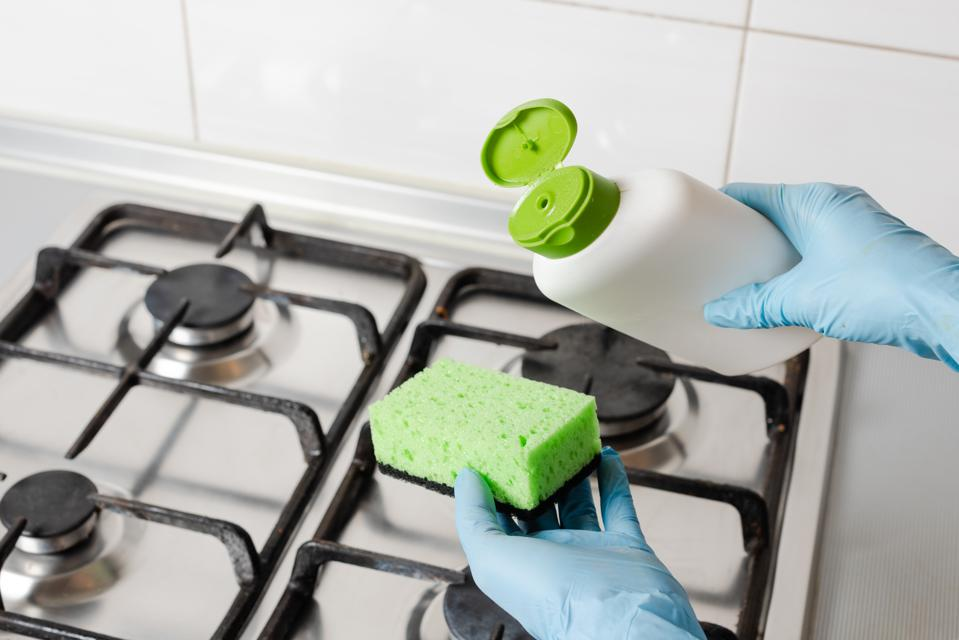 Pour washing detergent from bottle to green sponge