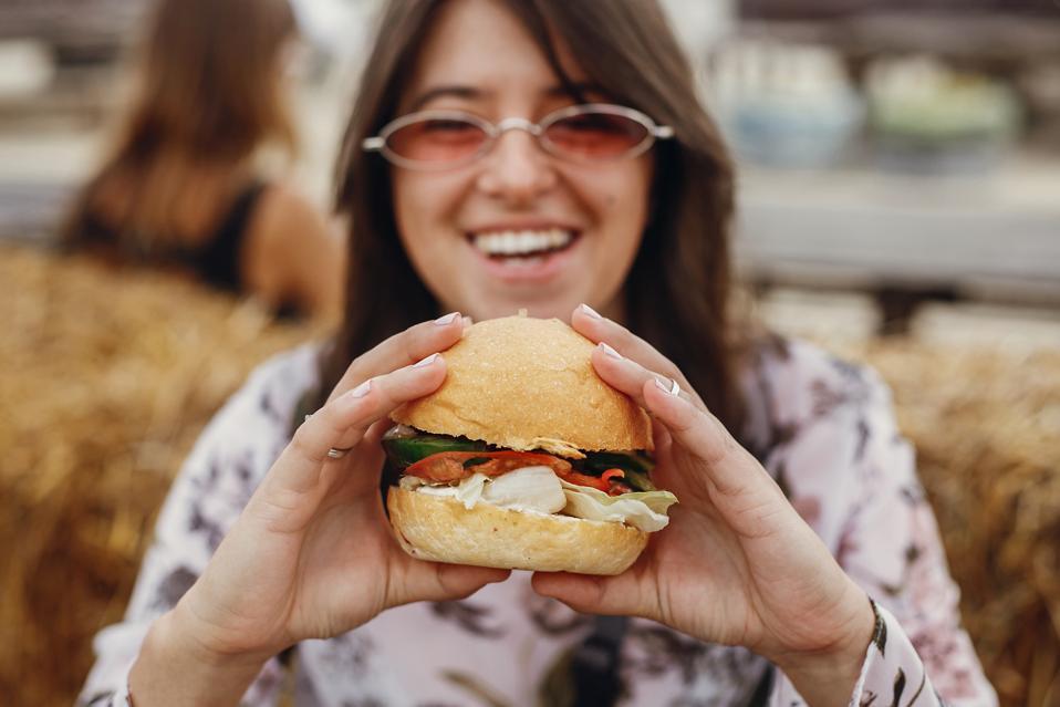 Woman in sunglasses eats vegan burger at street food festival.