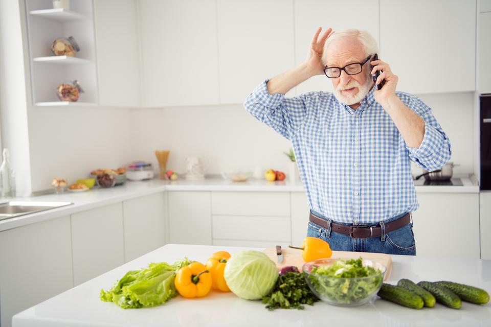 Close up portrait grey haired he his him grandpa hold head hand arm telephone smart phone wrong recipe listen new worried wear specs casual checkered plaid shirt jeans denim outfit light kitchen