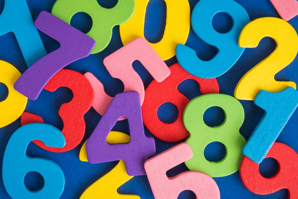 Close up of multicolored wooden numbers back to school abstract.