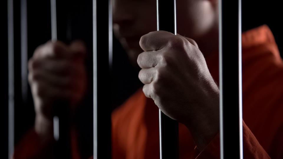 Desperate criminal holding jail bars feeling regret for committing crime closeup