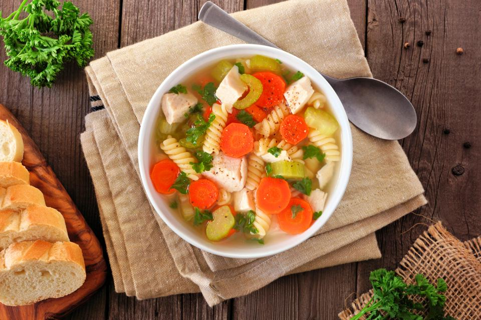 Homemade chicken noodle soup with vegetables, overhead table scene on wood