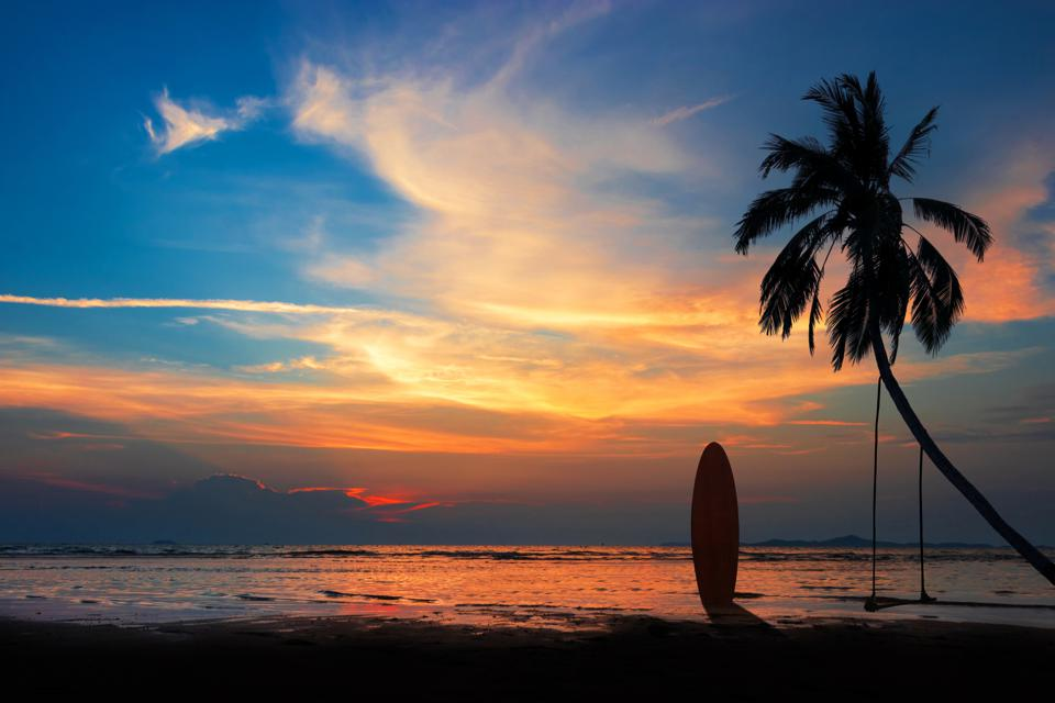 Silhouette of surfboard and coconut palm tree on the beach at sunset time with colorful sky.