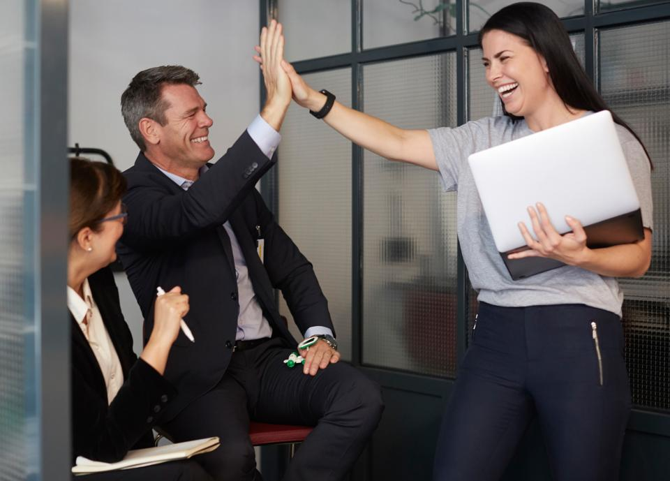 Cheerful creative businesswoman high-fiving with male bank manager during meeting in office