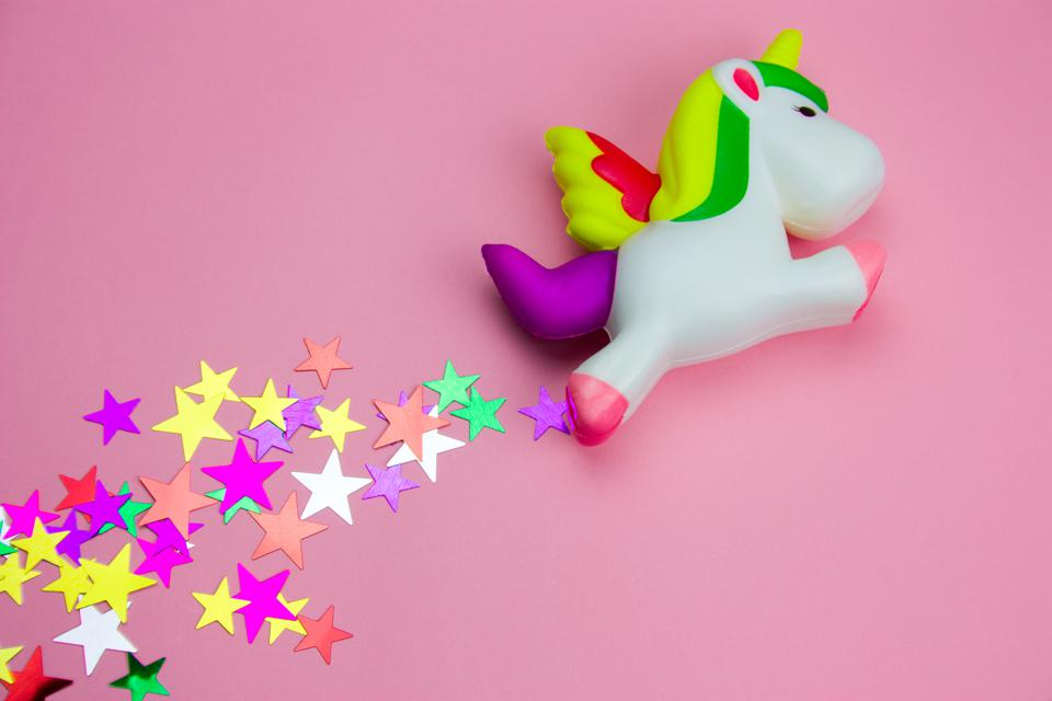 squishy toy  unicorn and glitters in the shape of stars on pastel pink background
