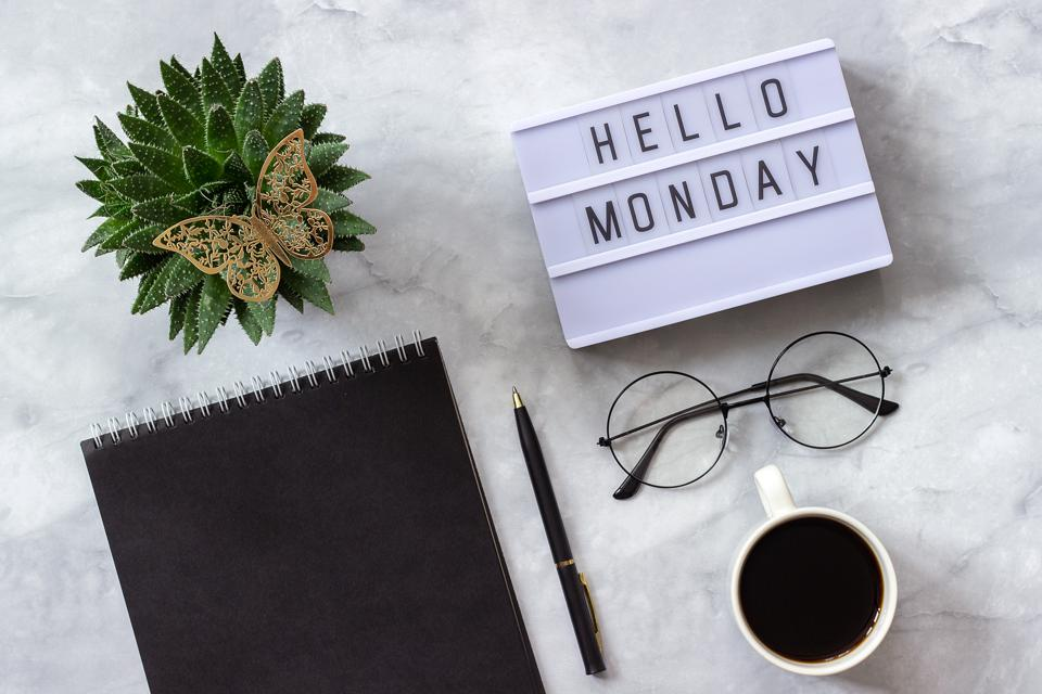 Office table desk. Lightbox text says hello monday. Black notepad, cup of coffee, succulent, glasses on marble background. Concept: motivation in the workplace.