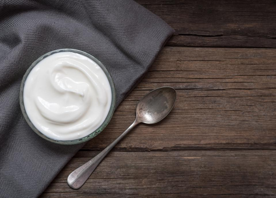 White yogurt in glass bowl on old wooden desk with spoon on right side.
