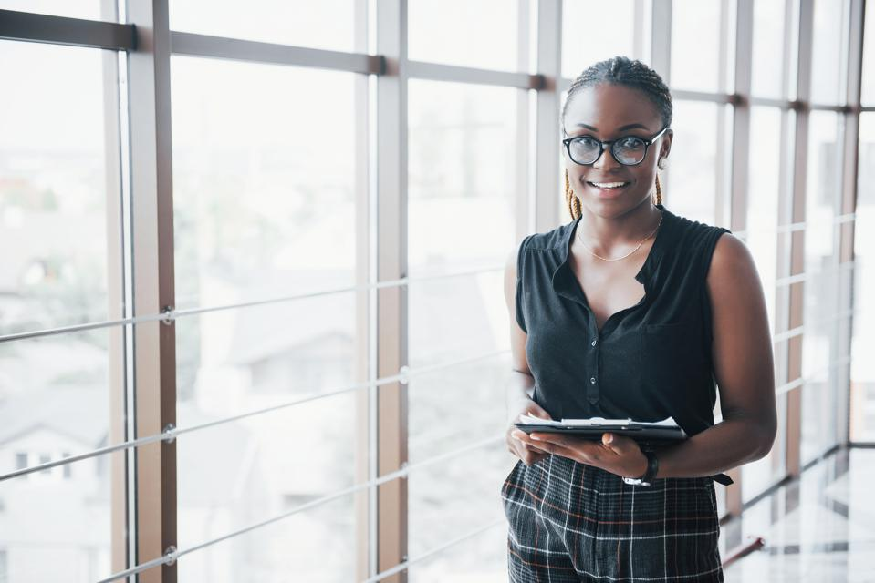 A thoughtful African American business woman wearing glasses holding documents