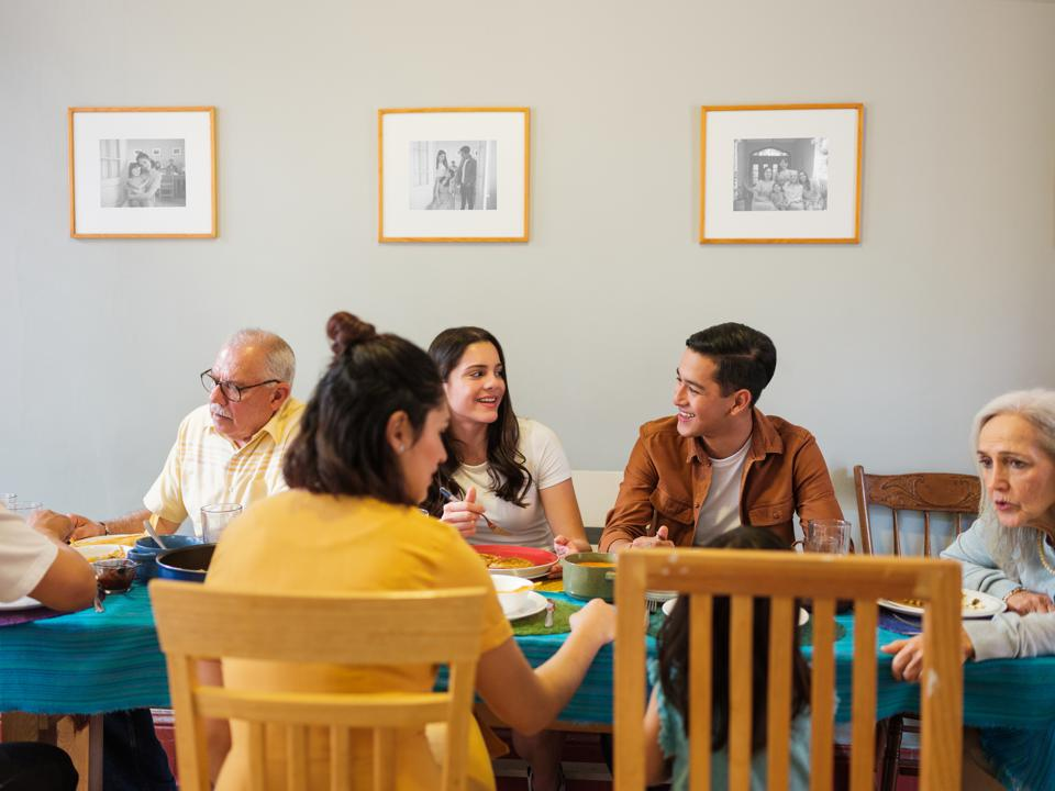 Intergenerational mexican family sitting and talking at lunch table