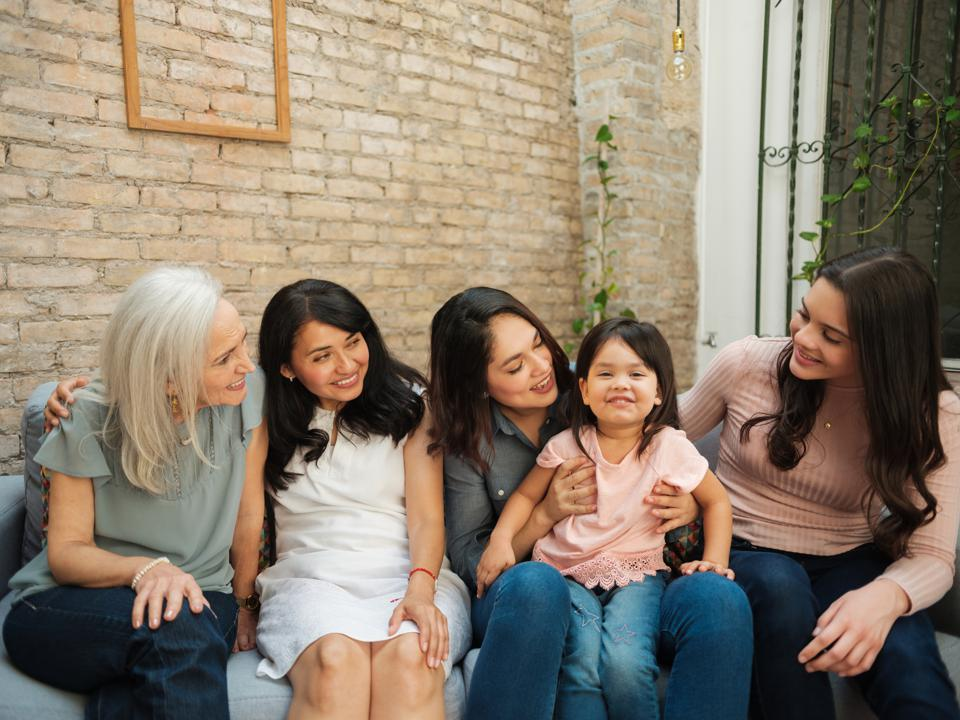 Intergenerational mexican women sitting and looking at girl