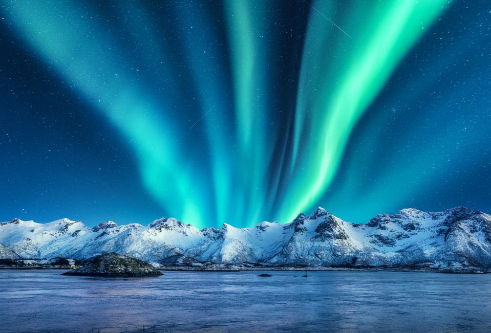 Aurora borealis above the snow covered mountains in Lofoten islands, Norway. Northern lights in winter. Night landscape with polar lights, snowy rocks, reflection in the sea. Starry sky with aurora
