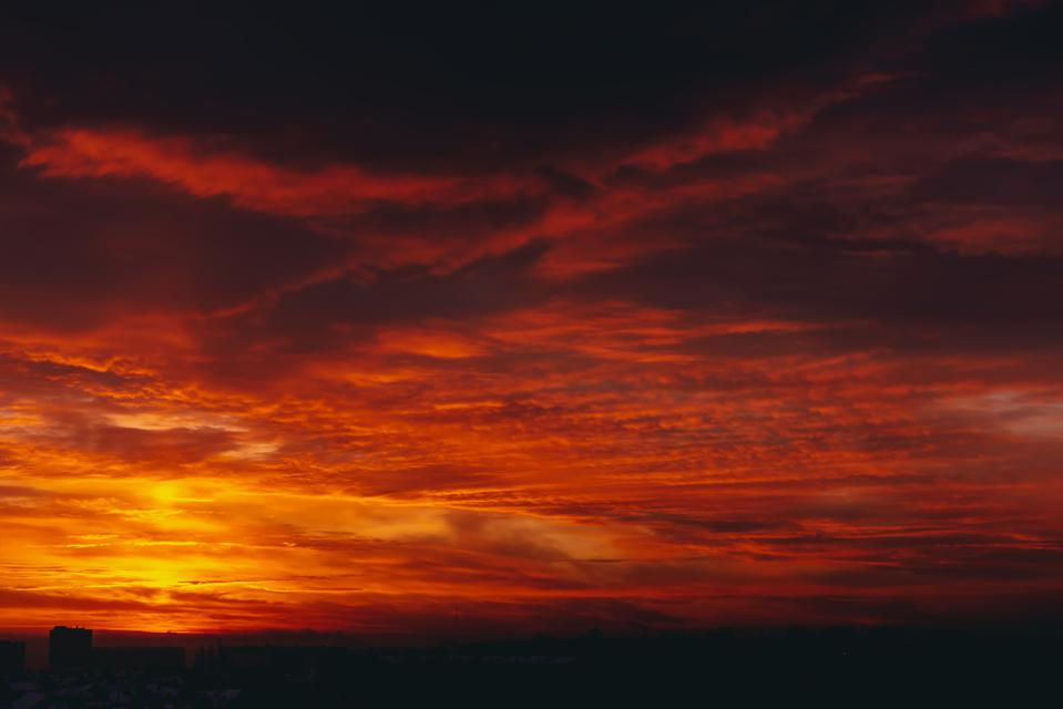 Fiery red blood vampire dawn. Amazing warm dramatic fire blue dark cloudy sky. Orange sunlight. Atmospheric background of sunrise in overcast weather. Hard cloudiness. Storm clouds warning. Copy space