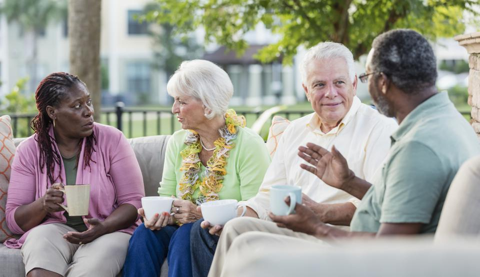 Two older couples hanging out on patio, conversing