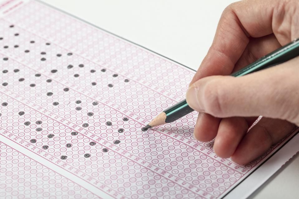 Student filling out the bubble sheet for the SAT exam.
