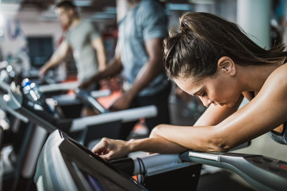 Sweaty athletic woman feeling exhausted on treadmill in a gym.
