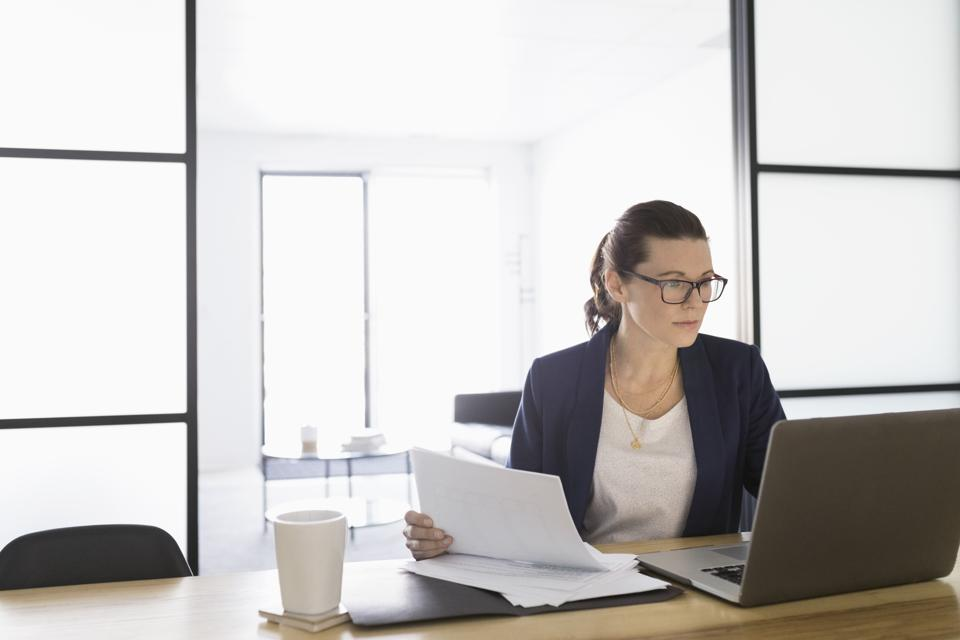 Focused businesswoman with paperwork working at laptop