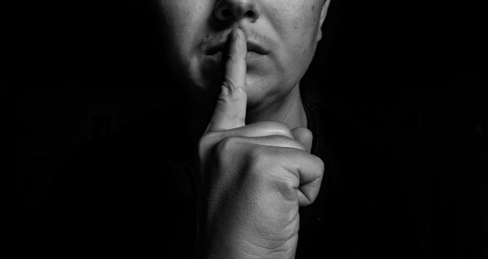 man with finger on lips in silence pose