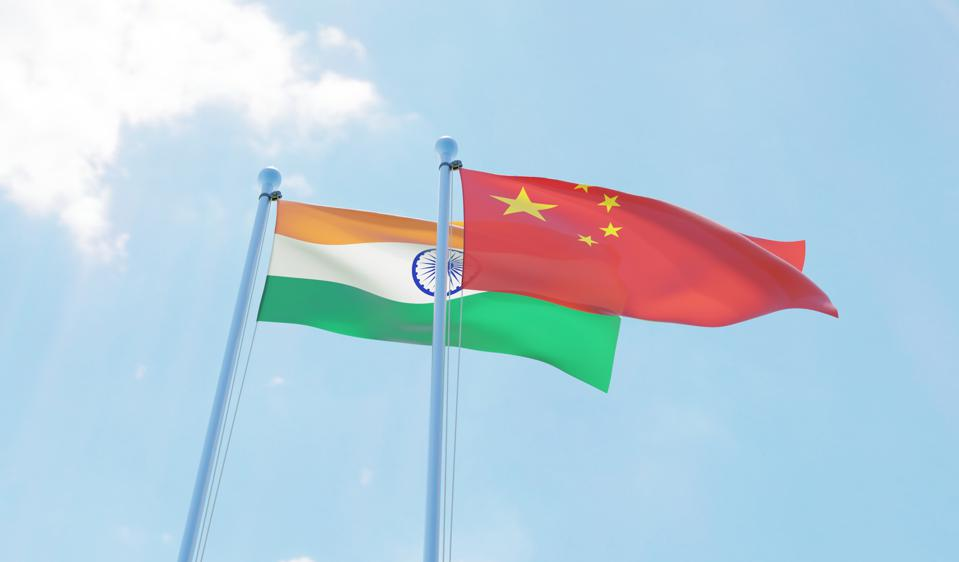 India and China, two flags waving against blue sky
