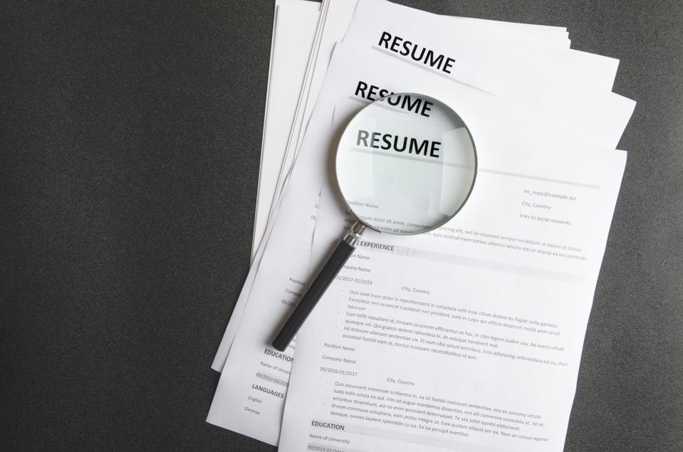 Top view of stack of resume files, magnifing glass.Concept of reviewing resume applications, searching for new employees