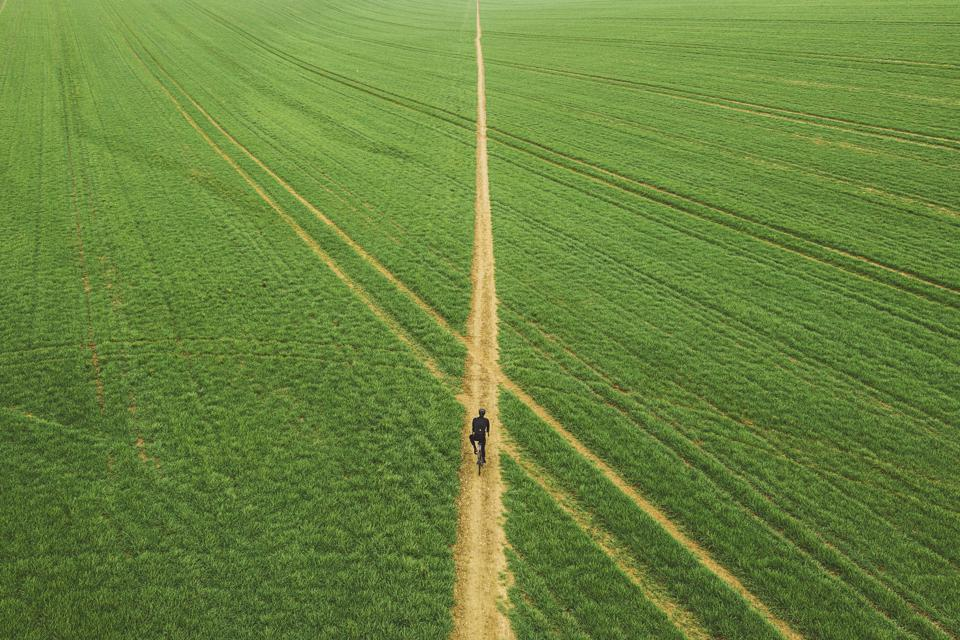 Drone view of cyclist on path through field