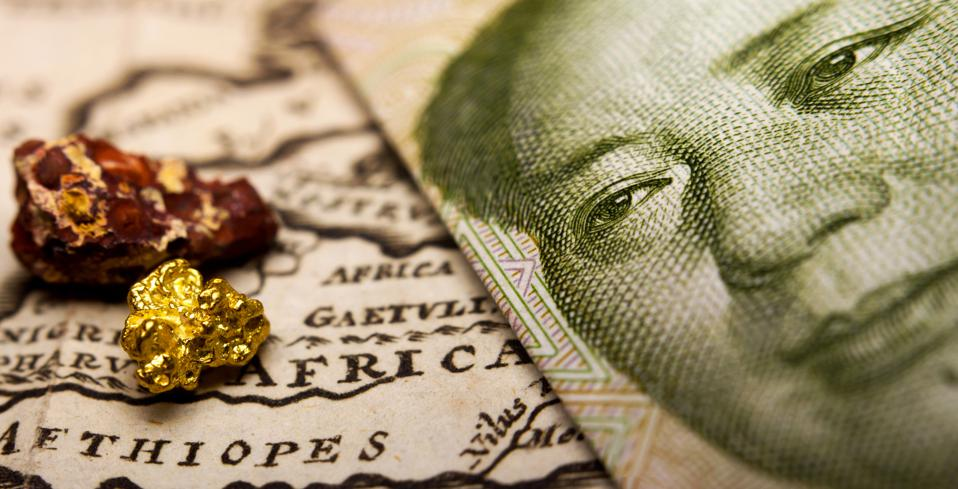 Chinese banknote and a gold nugget and rare earth metal on map of Africa