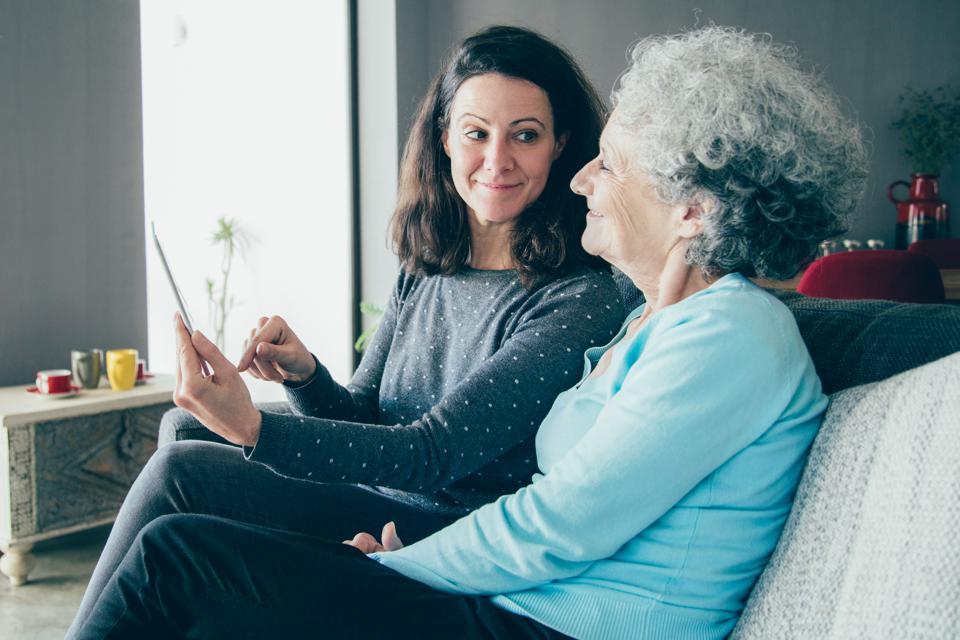 Smiling senior woman and her daughter using tablet computer