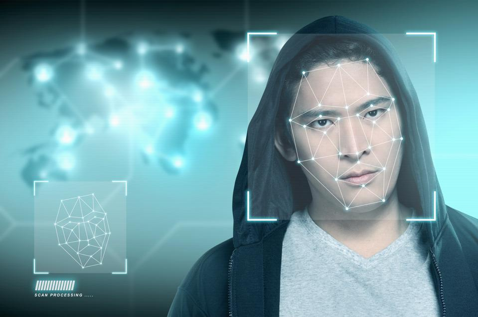Young asian man in black hoodie using face recognition