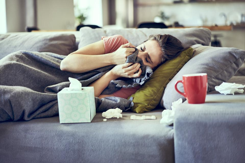 Sick woman trying to take a nap while lying on couch covered in blanket flu vaccine