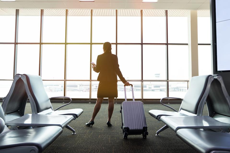 Image of businesswoman at airport looking at airplane taking off. Is now the time for an airline passengers' bill of rights?