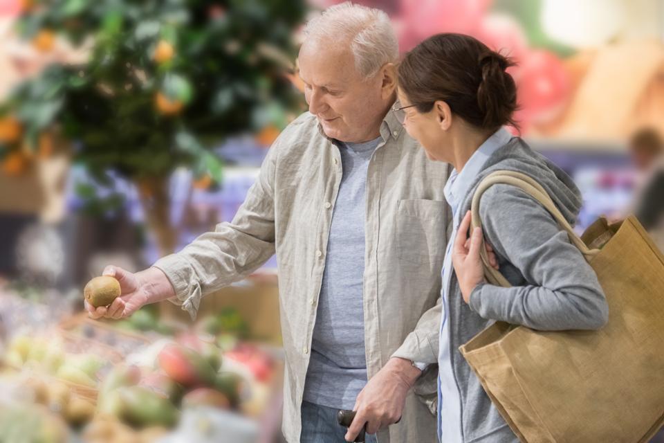 Senior man with home caregiver shopping