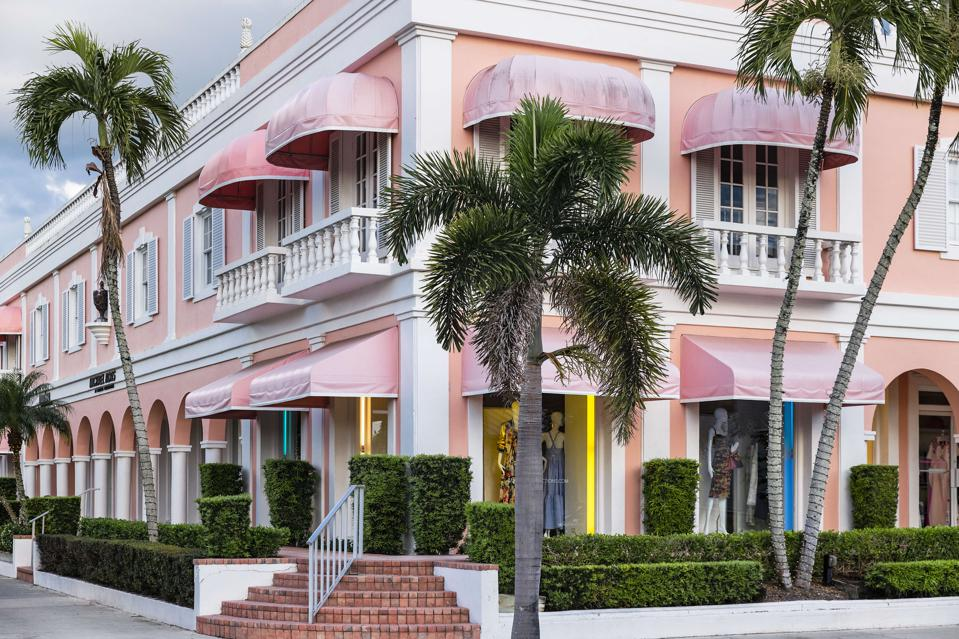 Pink store with matching awnings and Palm Trees of Marissa Collections Old Naples Florida.