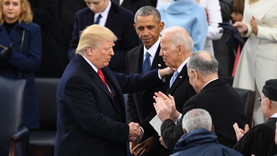 Former vice president Joe Biden shakes hands with Donald Trump at Trump's inauguration.