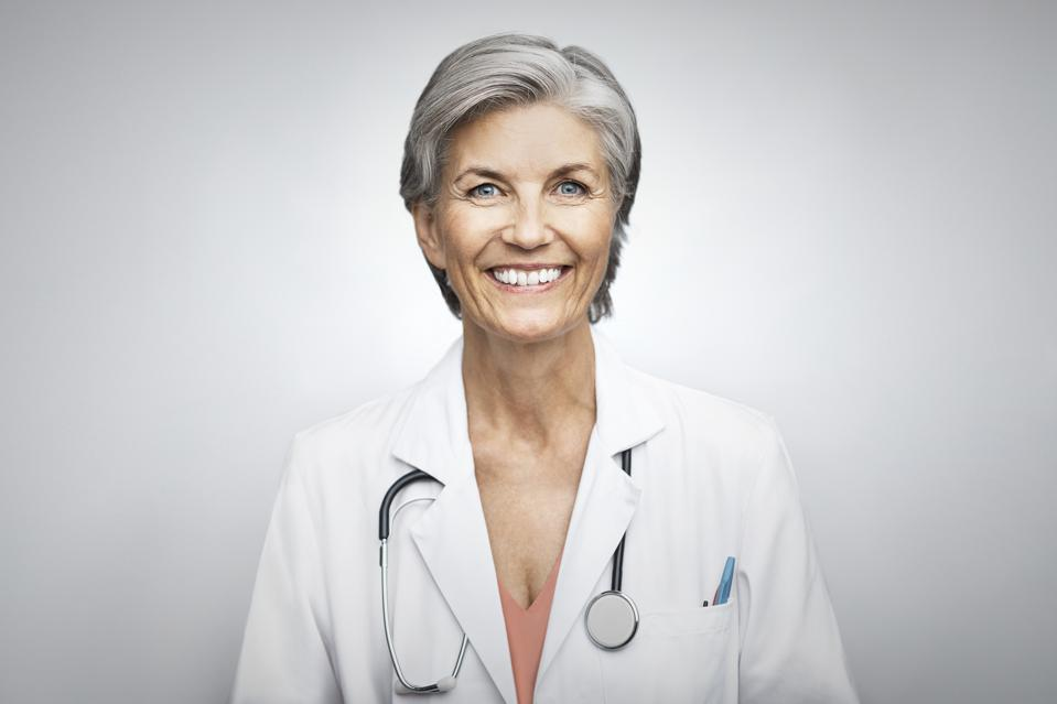 Attractive trustworthy senior female doctor smiling on white background