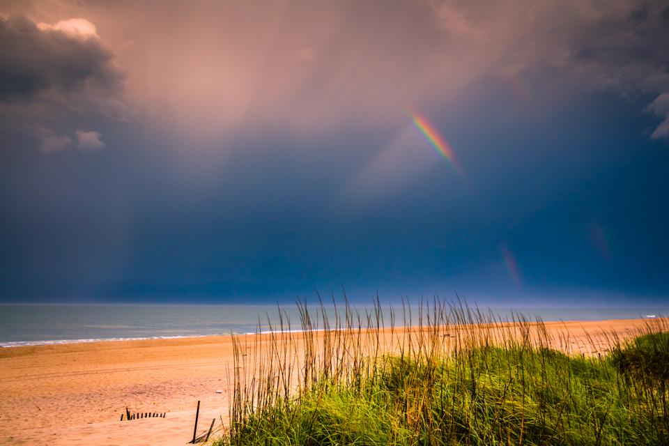 Partial rainbow over partial beach dunes with grass and clouds showing - horizontal orientation