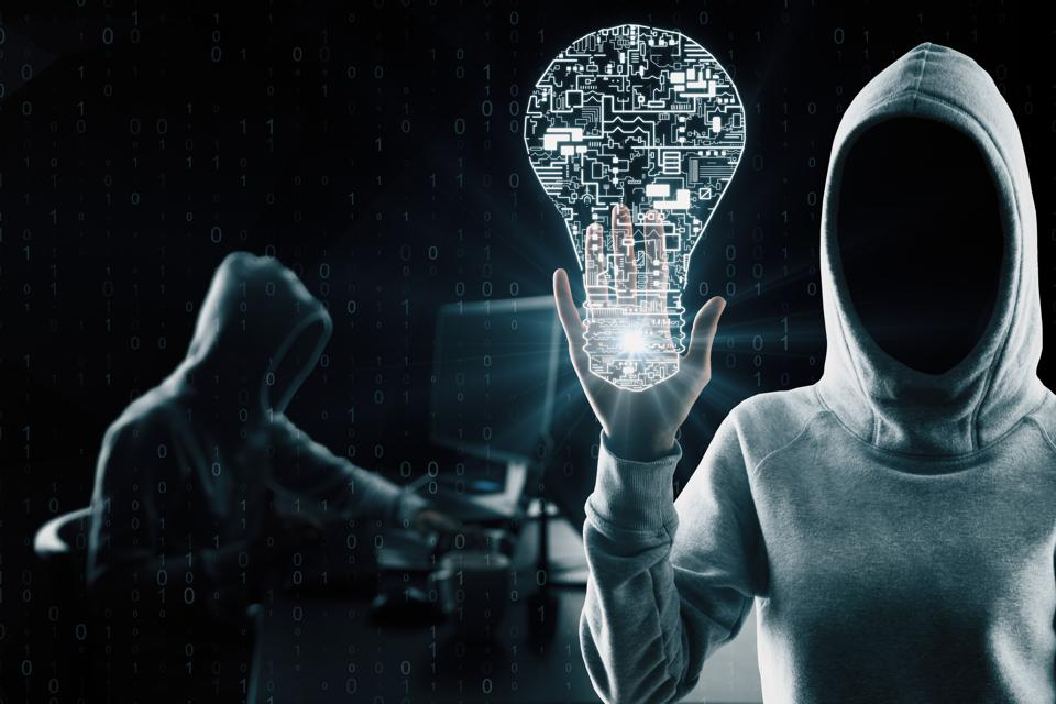 Hackers in hoodies holding a light bulb with circuit board imagery inside