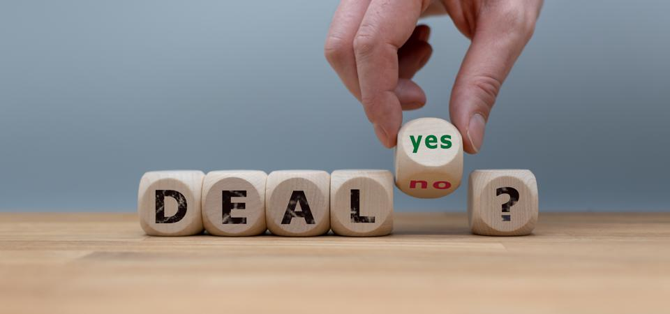 Deal or no deal? Hand turns a cube and changes the word ″no″ to ″yes″.