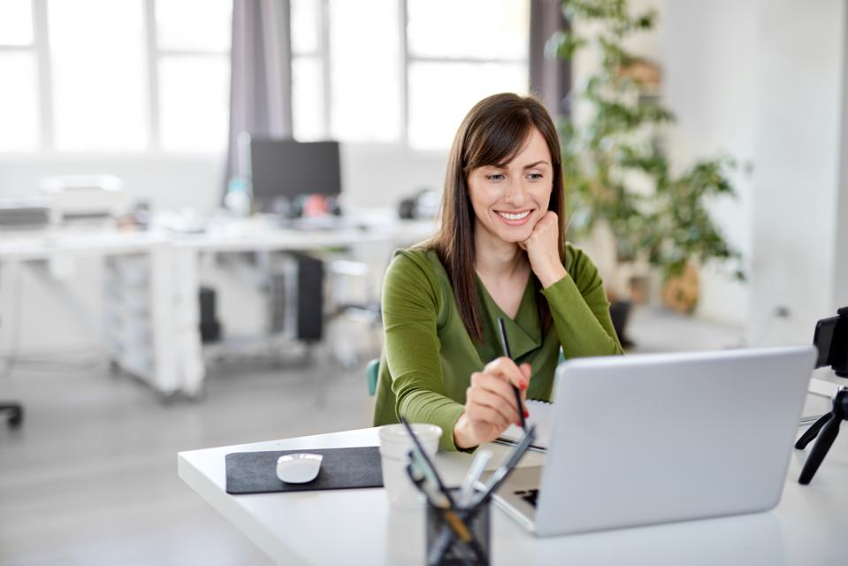Woman holding pencil an looking at laptop while sitting in office.