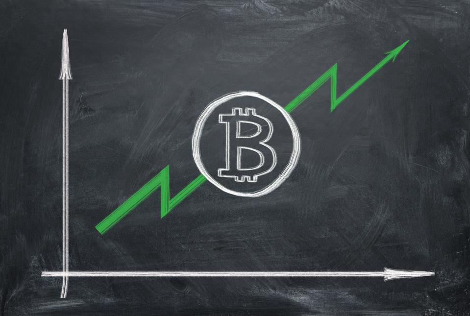 Growing graph of bitcoin (BTC) with green arrow on blackboard painting chalk.