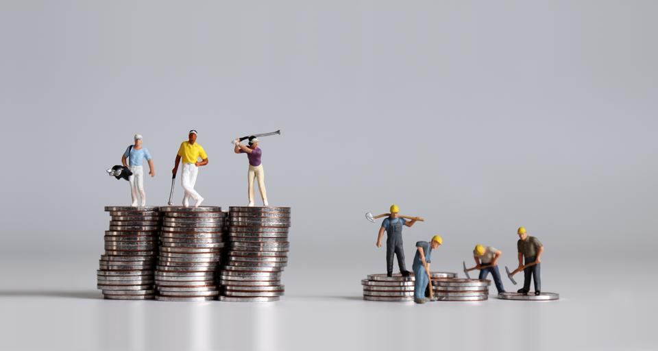 Miniature people standing on a pile of coins. A concept of financial inequality.