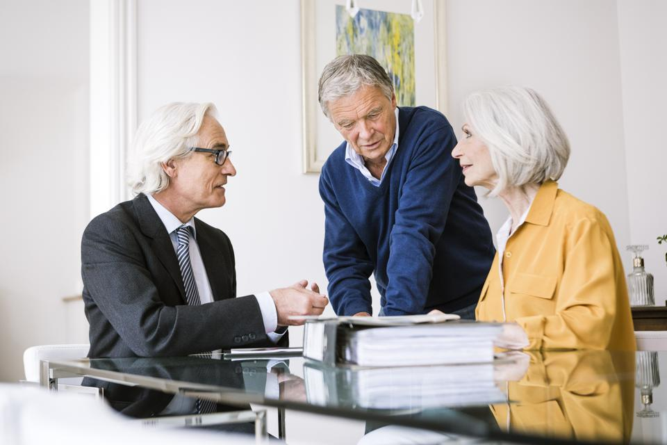Senior adults in business meeting discussing paperwork