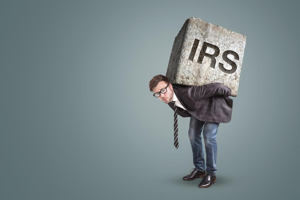 Entrepreneur carrying a large stone with engraved IRS letters