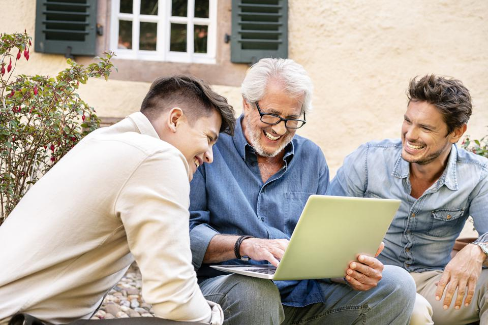 Three happy men of different age using laptop in garden