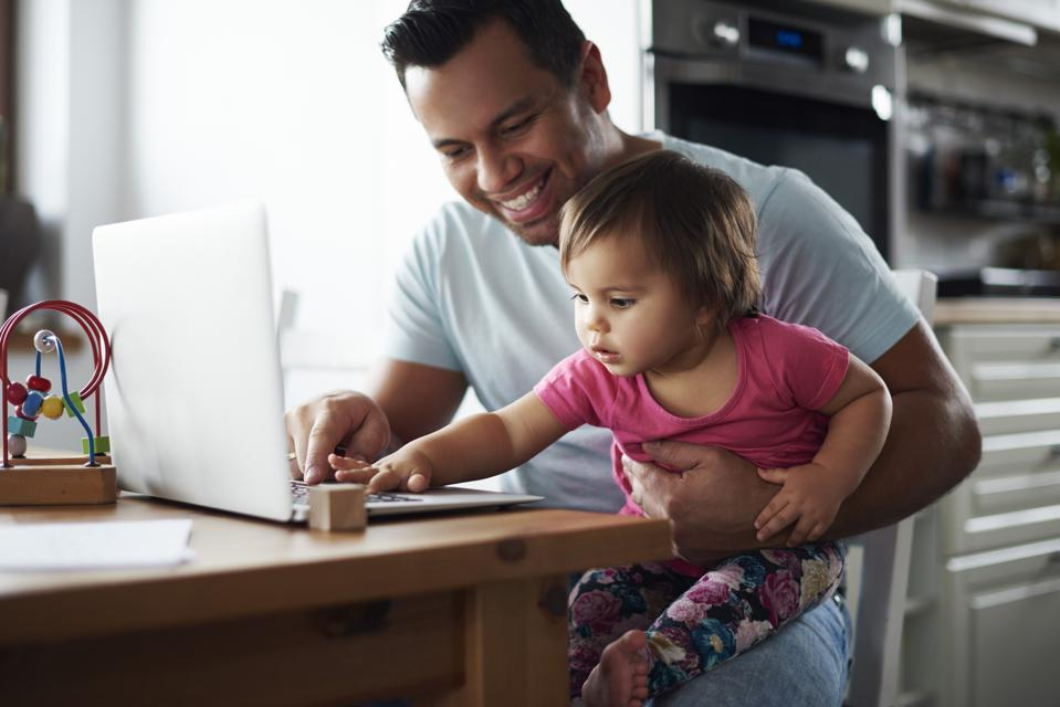 Smiling father and baby girl using laptop on table at home